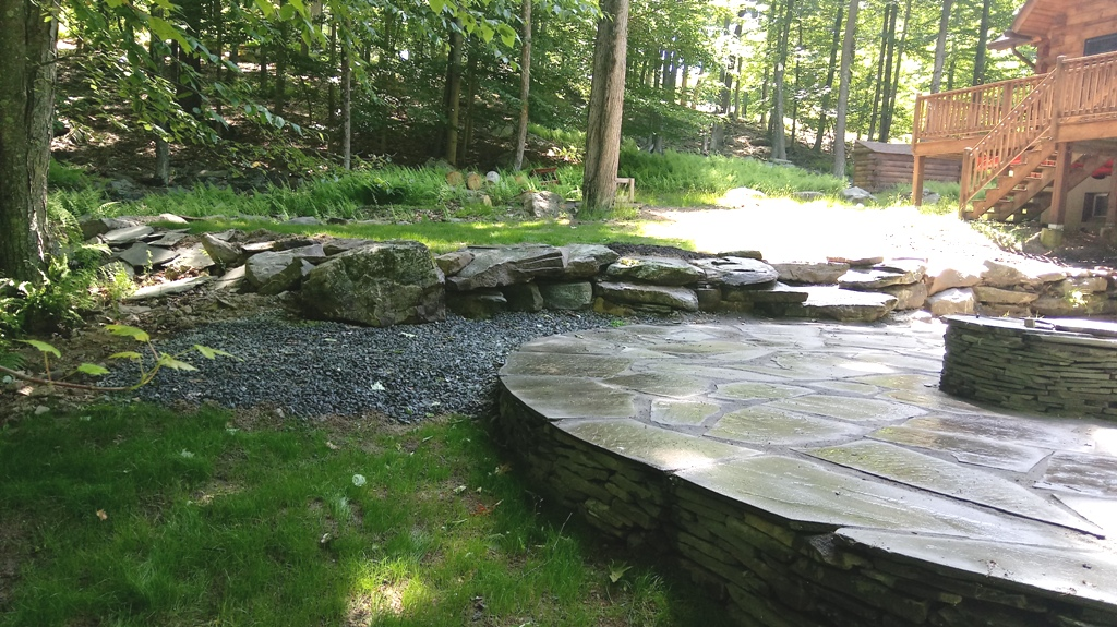 Repaired Round Bluestone Patio with Firepit and Boulder Retaining Wall by Apple Creek Landscaping, LLC.